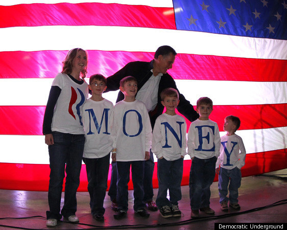 Mitt Romney standing in front of an American flag with a group of boys wearing tshirts that spell out MONEY
