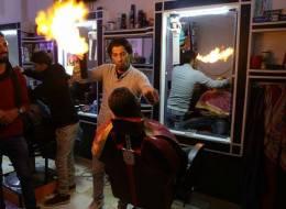 الحرق بالنار لتصفيف الشعر في غزة بدلاً من الكهرباء.. هكذا يتجنَّب الحلاق إشعال رأسك
