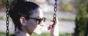 YOUNG WOMAN IS SWINGING ON A SWING IN A PARK