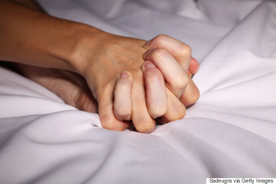 bed holding hands