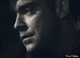 WATCH: Robbie Williams Plays A Criminal